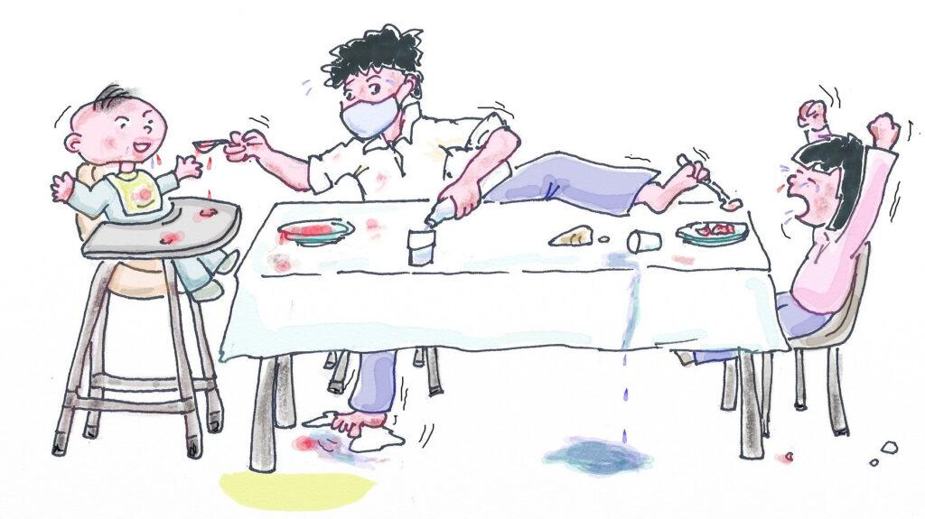 un papà cerca disperatamente di dare da mangiare ai due figli, uno piccolo e uno più grandicello, aiutandosi anche con un piede per mantenere il distanziamento fisico